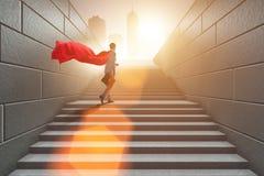 O super-herói do homem de negócios bem sucedido no conceito da escada da carreira Fotos de Stock Royalty Free