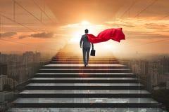 O super-herói do homem de negócios bem sucedido no conceito da escada da carreira imagens de stock royalty free