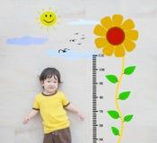 O suporte asiático feliz da criança do close up para a medida da altura com o girassol bonito dos desenhos animados na parede de  Imagem de Stock Royalty Free