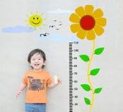 O suporte asiático feliz da criança do close up para a medida da altura com o girassol bonito dos desenhos animados na parede de  Foto de Stock