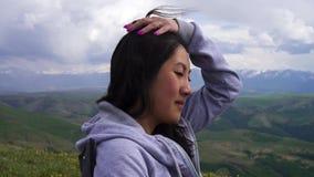 O suporte asiático novo da menina em um campo ventoso nas montanhas e endireita seu cabelo filme