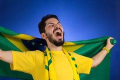 O suporte da equipa nacional de futebol está guardando o fla de Brasil imagens de stock royalty free