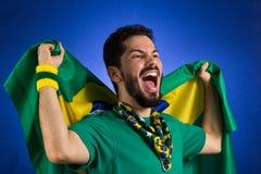 O suporte da equipa nacional de futebol está guardando o fla de Brasil imagens de stock