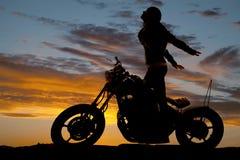 O suporte da motocicleta da mulher da silhueta entrega para trás imagem de stock