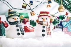 O suporte do boneco de neve entre a pilha da neve na noite silenciosa, ilumina acima o hopefulness e a felicidade no Feliz Natal  Fotos de Stock