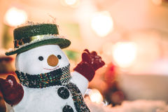 O suporte do boneco de neve entre a pilha da neve na noite silenciosa, ilumina acima o hopefulness e a felicidade no Feliz Natal  Foto de Stock