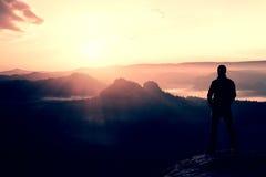 O suporte do caminhante no canto afiado da rocha do arenito em impérios da rocha estaciona e olhando sobre o vale enevoado e nevo imagem de stock