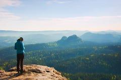 O suporte do caminhante no canto afiado da rocha do arenito em impérios da rocha estaciona e olhando sobre o vale enevoado e nevo fotos de stock