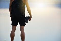 o suporte do homem ao lado do lago e guardar a luz da câmera e do sol refletem o Foto de Stock
