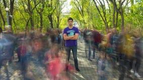 O suporte do homem no Ghost-como o fluxo da multidão, em árvores do verde do fundo Lapso de tempo vídeos de arquivo