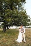 O suporte dos noivos no fundo da árvore, após a cerimônia de casamento Os recém-casados estão sorrindo, eles estão felizes Imagens de Stock Royalty Free