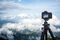 O suporte profissional digital da câmera de Dslr no tripé que fotografa a montanha, o céu azul e a nuvem ajardinam Fotografia de Stock