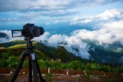 O suporte profissional digital da câmera de Dslr no tripé que fotografa a montanha, o céu azul e a nuvem ajardinam Imagem de Stock