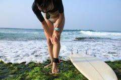 O surfista da mulher obteve a lesão de joelho ao surfar fotos de stock royalty free