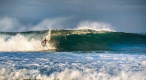 O surfista levanta-se em uma onda foto de stock
