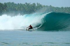 O surfista que desliga a parte inferior na onda grande, Mentawai é imagem de stock