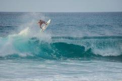 O surfista que salta uma onda em Rocky Point em Oahu, Havaí, EUA imagens de stock