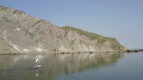 O surfista solitário do sup transporta-se lentamente ao longo da água azul calma ao longo da costa rochosa a pedregulhos filme