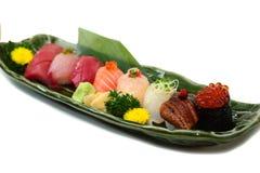O sushi ajustou a bandeja sortido do nigiri no ponto branco do foco seletivo do fundo da placa Fotos de Stock