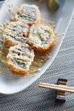 O sushi Califórnia rola com maionese da cobertura em matt e no hashi ao lado Imagens de Stock Royalty Free