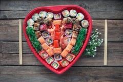 O sushi em um fundo de madeira velho da tabela com um coração deu forma à decoração foto de stock