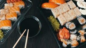 O sushi grande ajustou-se com variedade de rolos de sushi, maki, nigiri, gunkan em um fundo escuro à moda Molho e bambu de soja video estoque