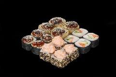 O sushi, rolos em um preto isolou o fundo Imagem de Stock Royalty Free