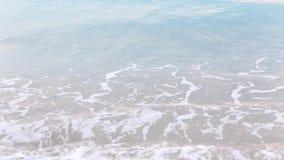 O swash do seawater acima da praia e das ondas que espirram lentamente na areia filme