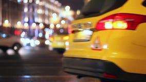 O táxi amarelo, contra o contexto da cidade da noite, começa a mover-se após uma parada curto video estoque