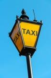 O táxi assina dentro Londres, Reino Unido Foto de Stock