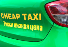 O táxi barato assina dentro inglês e o russo Imagens de Stock Royalty Free
