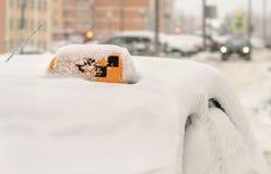 O táxi coberto com os passageiros de espera da neve estacionou no inverno com um quadriculado no telhado fotografia de stock