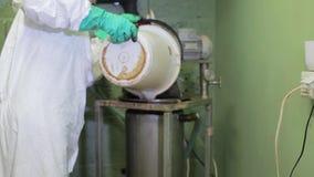 O técnico de laboratório derrama a água da cubeta branca no tanque de aço grande no porão da fábrica vídeos de arquivo
