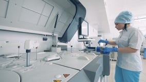 O técnico de laboratório põe amostras em uma cremalheira Cientista Working da mulher no laboratório 4K filme