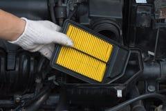 O técnico está mudando o filtro de ar novo para o carro Fotografia de Stock