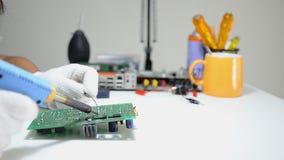 O técnico está soldando à placa de circuito eletrônica da cópia video estoque