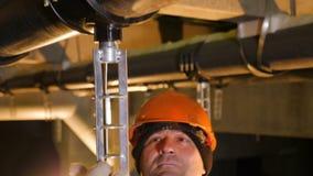 O técnico instala a peça de metal sob o gasoduto video estoque