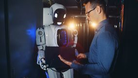 O técnico masculino liga um robô e regula seus ajustes