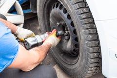 O técnico parafusa uma roda de carro pela chave pneumática fotos de stock