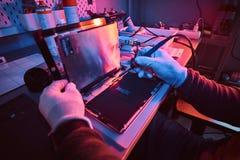O técnico repara um tablet pc quebrado em uma oficina de reparações Iluminação com luzes vermelhas e azuis imagens de stock royalty free