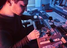O técnico repara um tablet pc quebrado em uma oficina de reparações Iluminação com luzes vermelhas e azuis fotografia de stock