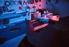 O técnico repara um tablet pc quebrado em uma oficina de reparações Iluminação com luzes vermelhas e azuis fotos de stock royalty free