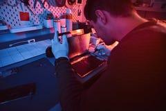 O técnico repara um tablet pc quebrado em uma oficina de reparações Iluminação com luzes vermelhas e azuis fotografia de stock royalty free