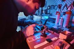 O técnico repara um tablet pc quebrado em uma oficina de reparações Iluminação com luzes vermelhas e azuis foto de stock royalty free