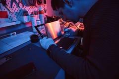 O técnico repara um tablet pc quebrado em uma oficina de reparações Iluminação com luzes vermelhas e azuis foto de stock