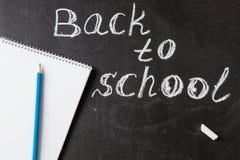 O título de volta à escola escrita pelo giz branco e o o caderno com corrigem no quadro preto da escola Fotografia de Stock
