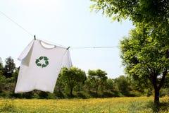 O t-shirt com recicl a secagem do logotipo no clothesline Foto de Stock
