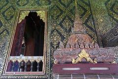o Tailandês-estilo decorou a janela e dourou a parede, com a caixa do scripture na prateleira de madeira cinzelada em Wat Mahatha foto de stock royalty free