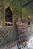 o Tailandês-estilo decorou a janela e dourou a parede, com a caixa do scripture na prateleira de madeira cinzelada em Wat Mahatha fotos de stock
