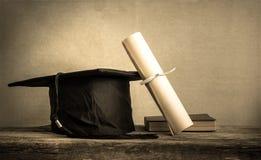 o tampão da graduação, chapéu com papel do grau na tabela de madeira vazia apronta-se fotografia de stock royalty free